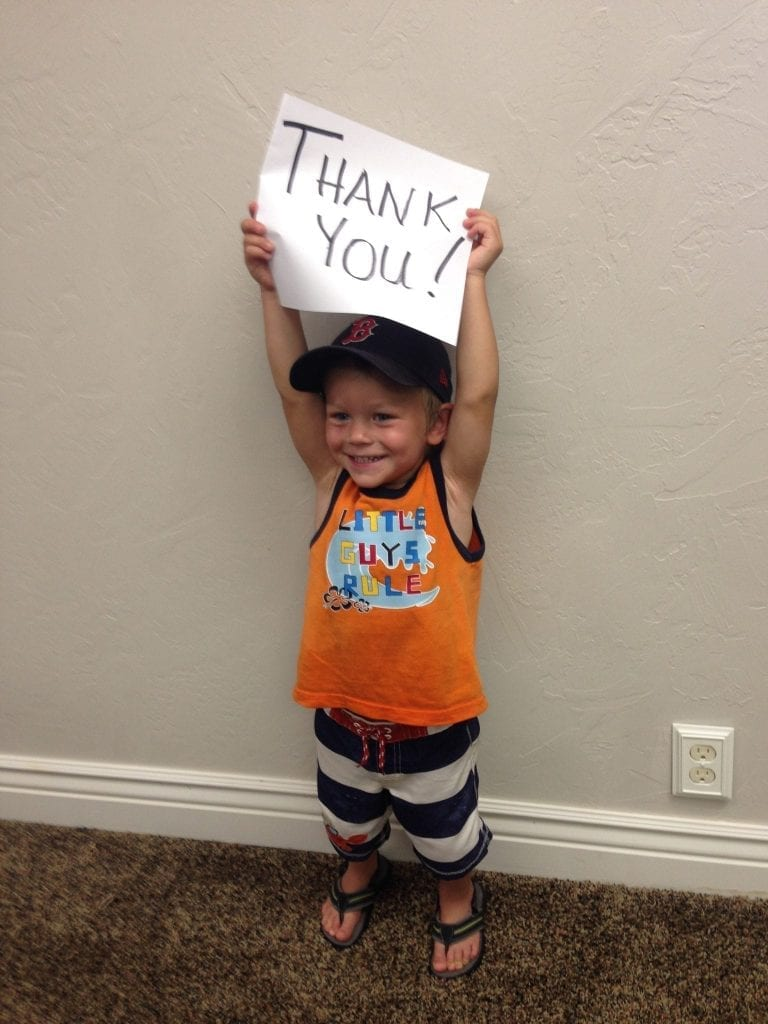 child holding 'thank you' sign