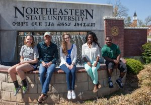 NSU students in front of entry sign