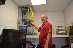 Superintendent, Bruce Shelley looking at network equipment