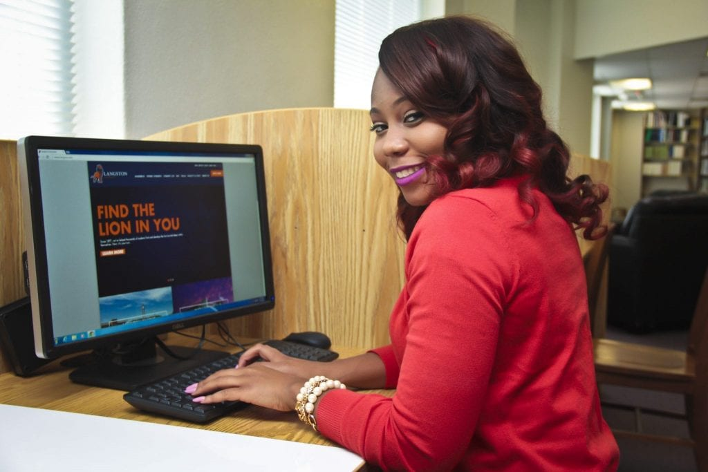 Langston University student using a computer in the library.