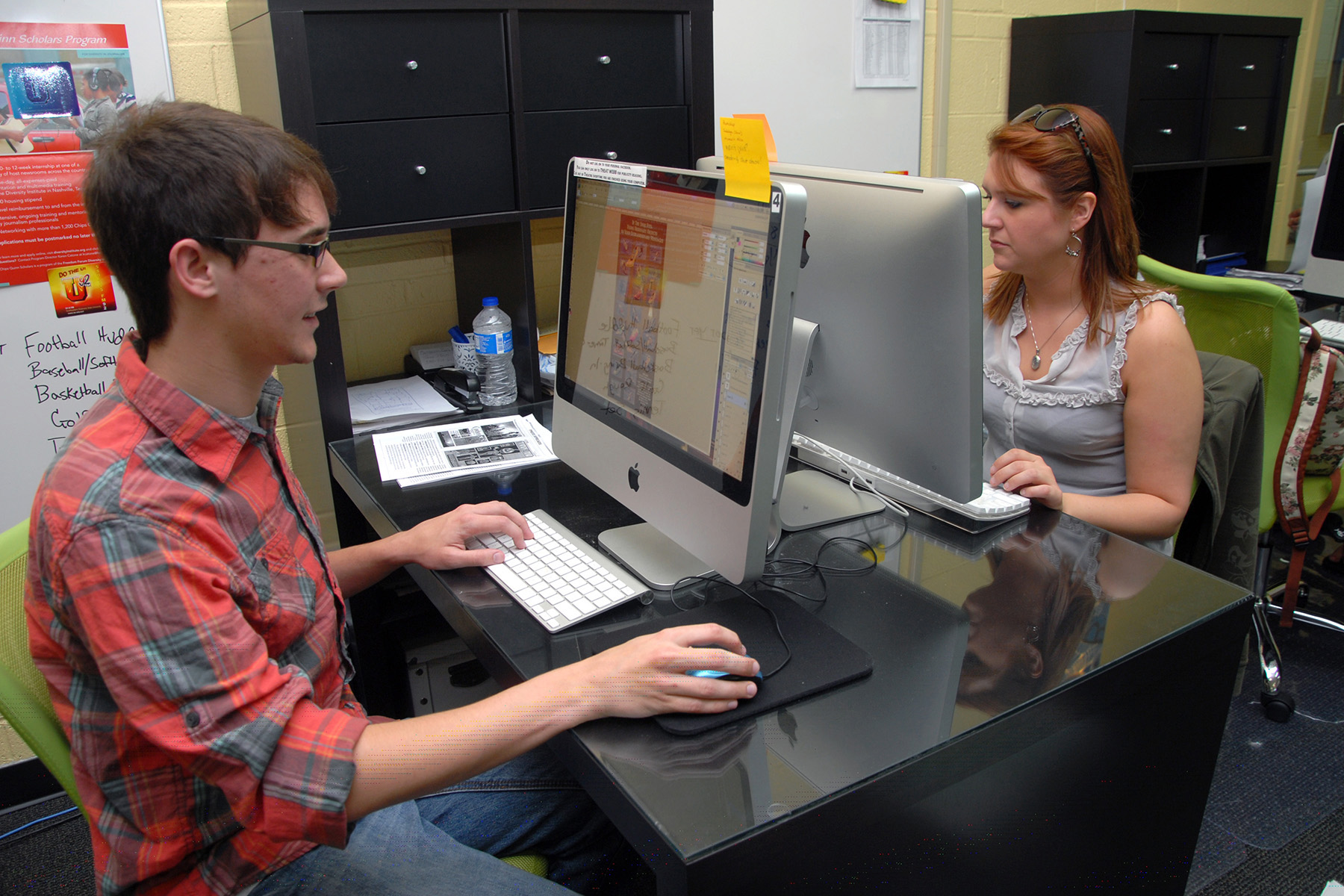 Male and female student using computers