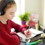 Preteen girl working on homework using tablet