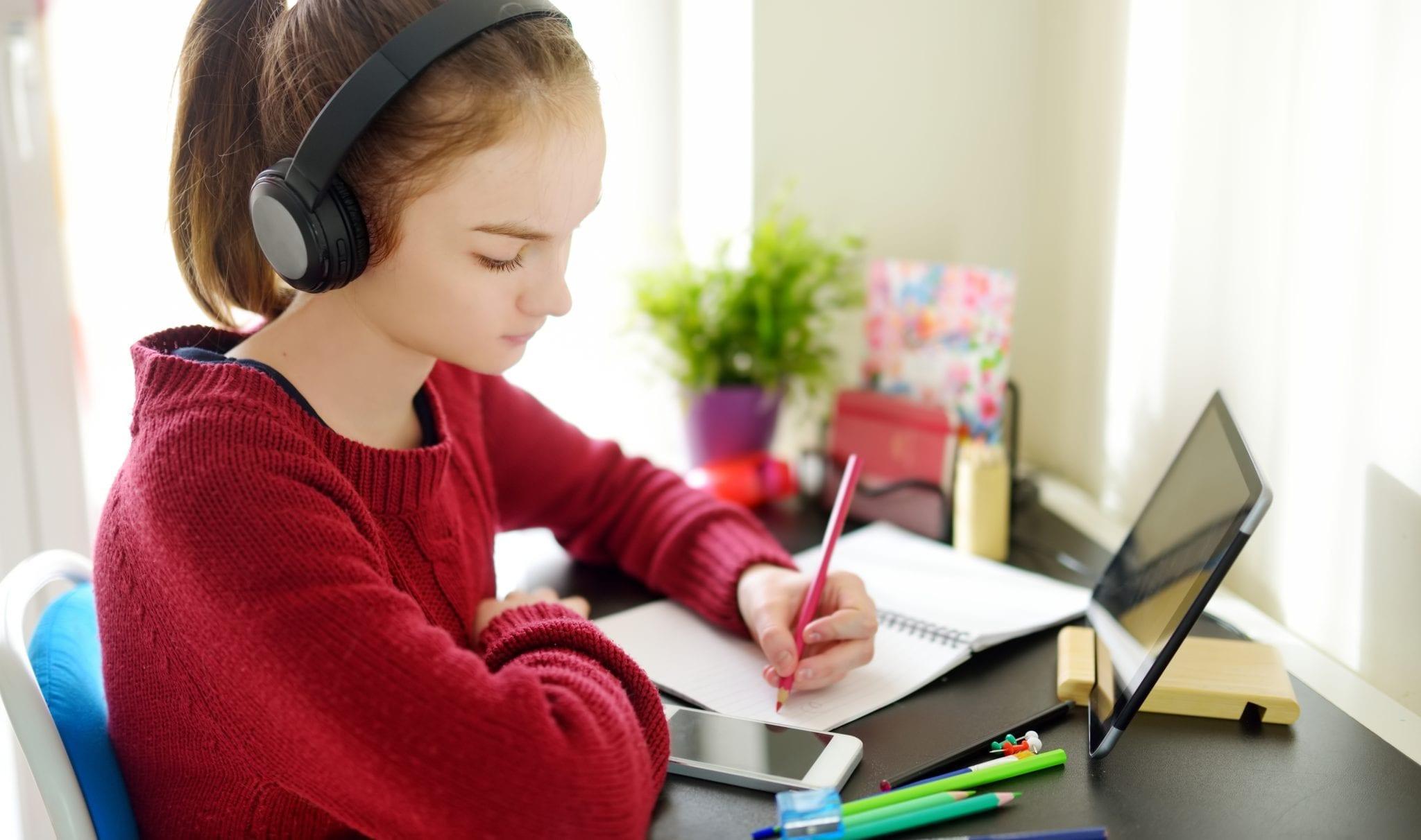 Preteen girl working on homework using tablet